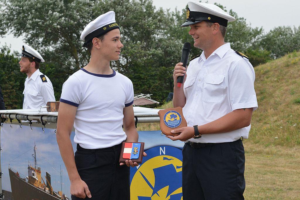Gilbèrt de Bock, als vicevoorzitter van het Zeekadetkorps Nederland wisselt schildjes met een Belgische Marinekadet.