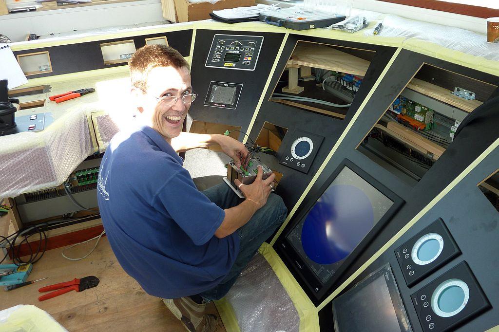 Richard van den Donker installeert voor Dutch Marine Technology apparatuur in een stuurhut.