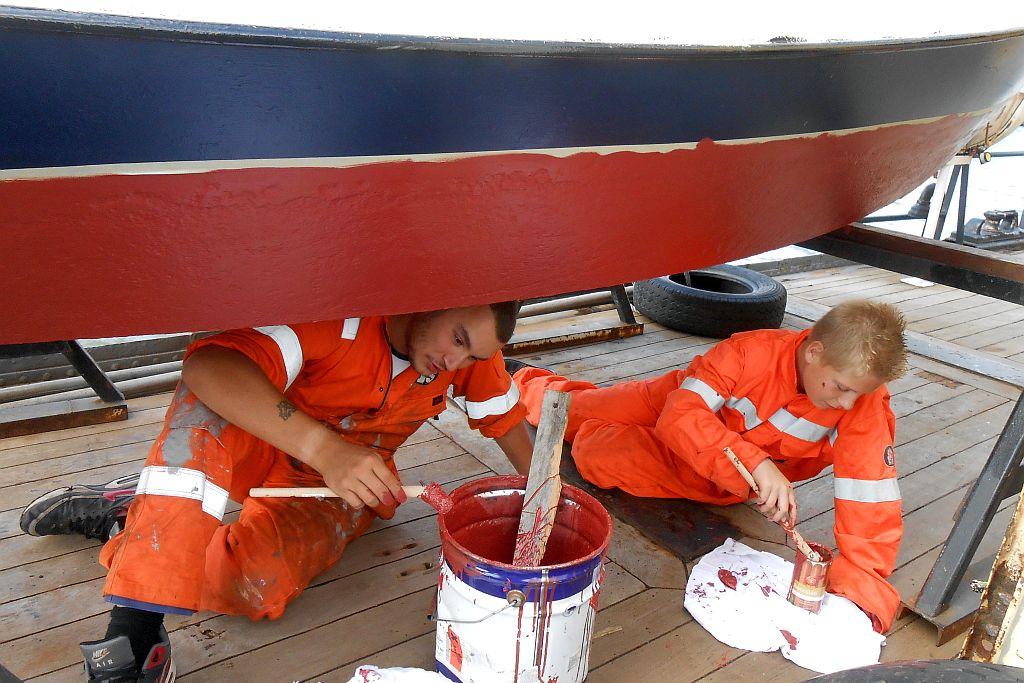 Jonge zeekadetten werken samen met ervaren korpsleden aan het onderhoud van de vaartuigen (ZKK Rotterdam).