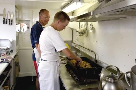 Een zeekadet aan het koken in de kombuis